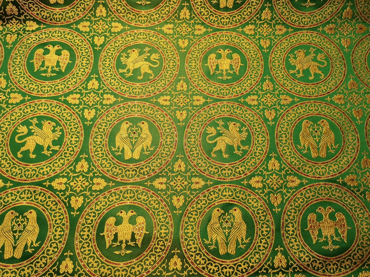 Зелёная ткань, расшитая разнообразными символами с животными